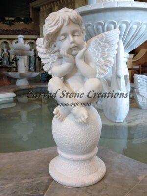 Carved angel cherub sculpture on ball.